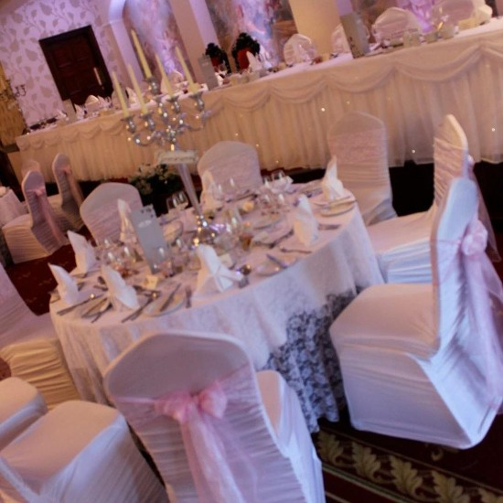 White vintage #laceoverlay with matching sashes with pink organza. White ruffled #chaircovers & #fairylight top table skirt. Silver #candelabras. #wedding #tullyglass