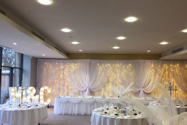 Fariylight backdrop, top table skirt, centrepieces & light u...